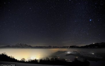 """Alps at Night"" showing the starry sky above a misty Alpine valley and village lights in Austria"